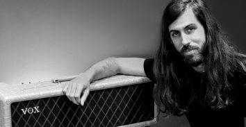 artist, Wayne Sermon, leaning on VOX amplifier